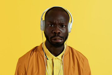 Man in white headphones listening music and making funny face