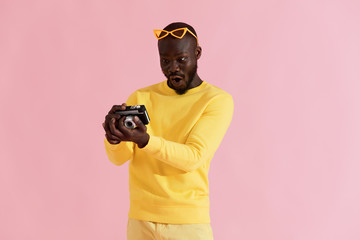 Surprised man looking at photos on camera on pink background