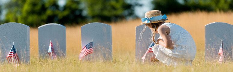 panoramic shot of kid in dress and straw hat sitting near headstone with american flag in graveyard