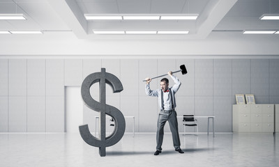 Determined banker man in modern office interior breaking dollar figure