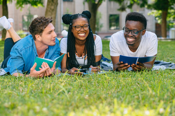 Multi-ethnic group of students friends lying on grass talking laughing reading books while doing homework at park in sunny meadow. Education and Friendship Concept. Black woman laughing at funny joke.