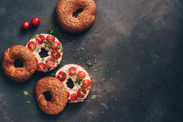 Homemade bagel sandwich with cream cheese, cherry tomatoes and basil sprinkled with sesame and flax seeds, dark rustic background. Overhead view, copy space.