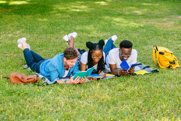 Front view of three happy multiethnic students studying reading notes together lying on the grass in a park. Education and friendship concept.