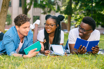 Front view of three happy multiethnic students lying, talking, joking together together on green lawn high school university campus. Education and Friendship Concept.
