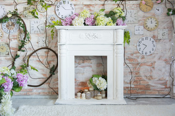 White decorative fireplace with flowers and candles.