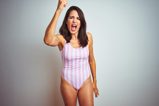 Young beautiful woman wearing striped pink swimsuit swimwear over isolated background angry and mad raising fist frustrated and furious while shouting with anger. Rage and aggressive concept.
