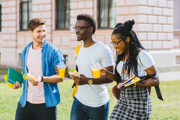 Group of three positive multiethnic students people coworkers talking, sharing ideas during lunch break standing outdoor university campus with books and backpacks. University education concept.