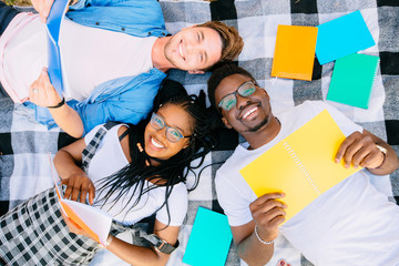 Top view of group three aucasian and african american students lying with notebook and looking away. Multiethnic team preparing to examinations in university park outdoors.
