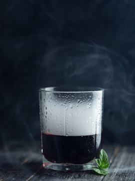 Smoke in a glass with red alcohol