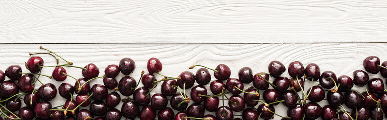 Foto auf Acrylglas Kirschblüte panoramic shot of fresh, sweet, red and ripe cherries with droplets on wooden surface