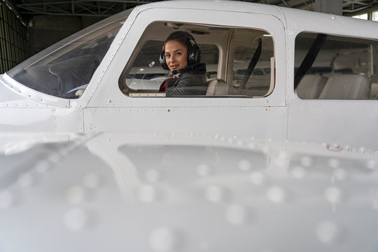 Exterior View of Aircraft and Beautiful Woman Pilot With Headset in the Cockpit