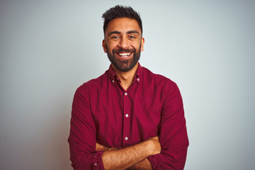 Young indian man wearing red elegant shirt standing over isolated grey background happy face smiling with crossed arms looking at the camera. Positive person.