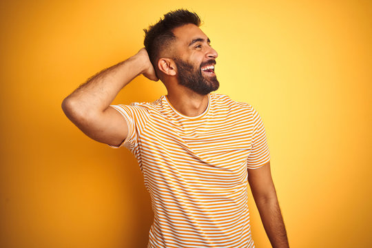 Young indian man wearing t-shirt standing over isolated yellow background smiling confident touching hair with hand up gesture, posing attractive and fashionable
