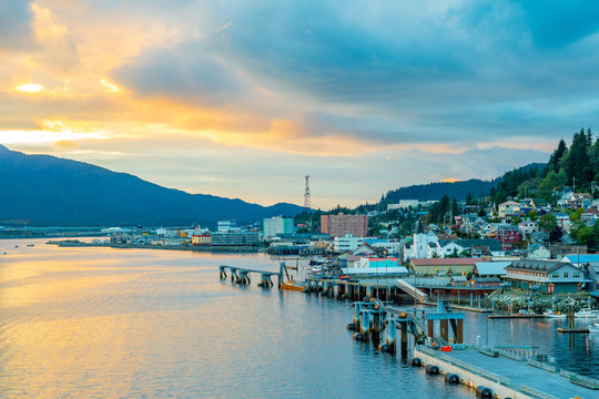 Sunset from the coast in Ketchikan, Alaska. Landscape coastal view along the ocean with buildings along the bay and mountain in background as the evening sun colors the cloudy/ overcast autumn sky.