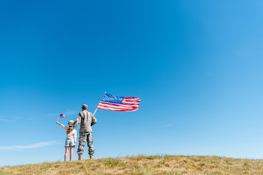 back view of kid in straw hat and military man holding american flags