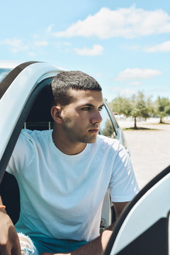 Young blue-eyed man and modern clothes getting off his car