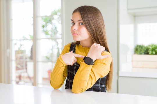 Young beautiful blonde kid girl wearing casual yellow sweater at home In hurry pointing to watch time, impatience, looking at the camera with relaxed expression