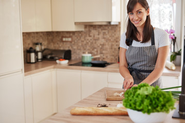 Smiling Caucasian female chef in apron chopping leek in kitchen and preparing dinner. Preparation of domestic food concept.