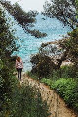 woman in raincoat walking to the sea by trail between trees