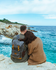 couple sitting on the cliff looking at sea