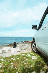 woman sitting at rock near suv car at seaside enjoying the view