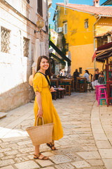tourist woman in yellow sundress walking by small croatian city street
