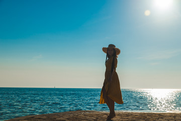 young pretty smiling woman in yellow sundress walking by stone beach