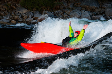 No need for a paddle. Kayaker rides a wave on the Lochsa River in Idaho.
