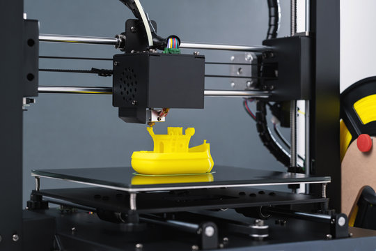 Printing on 3D printer figurines toys ship from yellow plastic close-up. Clear movements of the print head and printer working platform. The potential of modern technology 3D printing. Plastic reel
