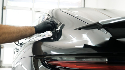 Staff wear Chemical protective clothing at work. Automobile industry. Car wash and coating business with ceramic coating.Spraying the varnish to the car. Concept of: Car protective, Service, Shine.