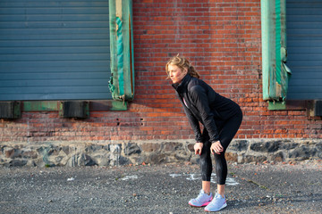 A fit, blonde female runner catches her breath near an old brick warehouse in downtown Spokane, Washington.