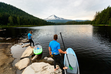 A man and woman prepare to stand up paddleboard at Trillium Lake, a popular recreation spot near the base of Mount Hood, Oregon.