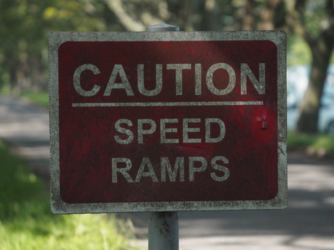 A speed ramps sign besides a road.