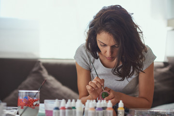 Brunette woman of latin race painting small figures with a white background.