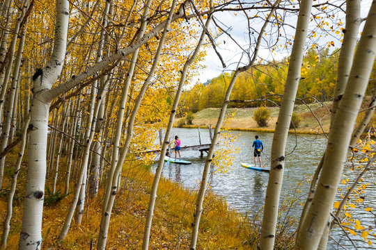 A man and a woman enjoying an afternoon on their inflatable stand up paddle boards while SUPing among the aspen trees in an alpine lake in the San Juan Mountains, Colorado in autumn.