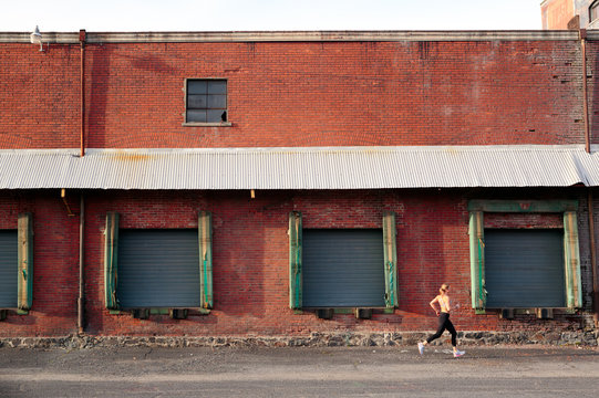 A fit, blonde female runner runs past an old brick warehouse in downtown Spokane, Washington.