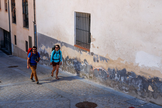 A man and a woman trek through the medieval streets of the old town section of Cuenca, Spain, a UNESCO World Heritage Site..
