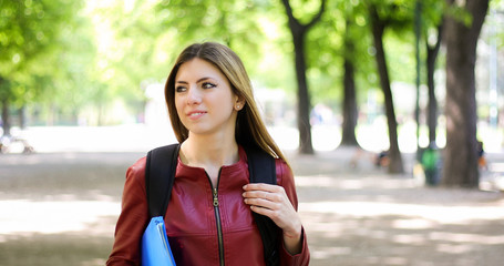 Female student walking outdoor in the park and smiling