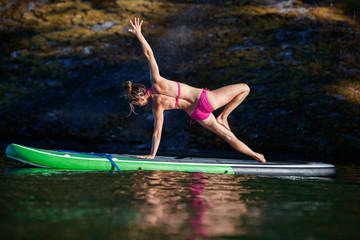 A woman does yoga on a stand up paddle board at sunset in Lake Pend Oreille in north Idaho in summer.
