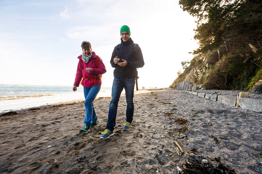Bolinas Beach, California, USA: A mother and her son collecting rocks and shells at the beach.