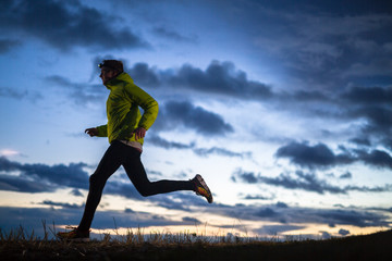 A male runner wearing a headlamp running at dusk in north Idaho.