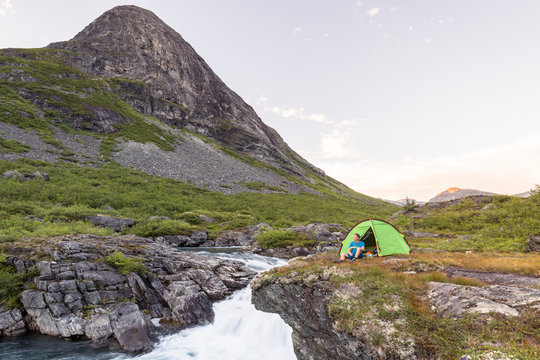 Eidsdalselva, M¯re og Romsdal, Norway: A male hiker at his camp on a cliff by the river.