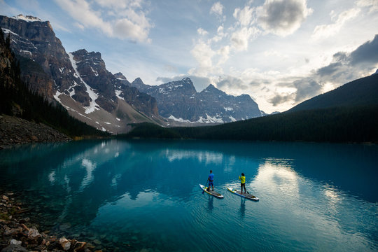 A couple stand up paddle board at Moraine Lake in Banff National Park in Canada.