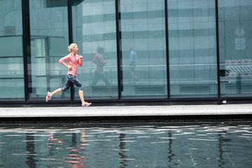 European Quarter, Stuttgart, Baden-W¸rttemberg, Germany: A female runner running along the glass walls of an office building that shows her reflection.