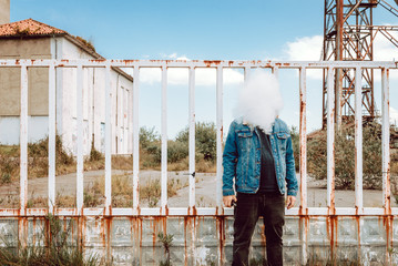 Man exhaling vape cloud in front of face while standing by fence