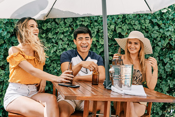 two young women and a man having a good time outdoor