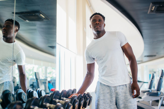 African American man picking up a dumbbell from the rack and looking outside at gym. Male weight training person holding sport equipment with serous look in fitness center