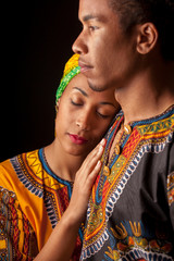 Couple of young attractive African in bright ethnic clothes standing and bonding