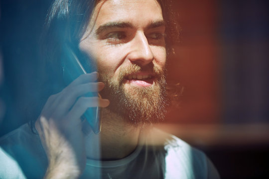 Young bearded handsome man in cafe behind window talking on phone
