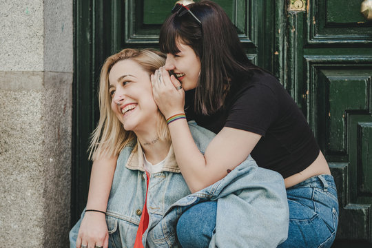 Young woman embracing and telling secret to pretty girlfriend laughing while sitting near entrance of building on city street